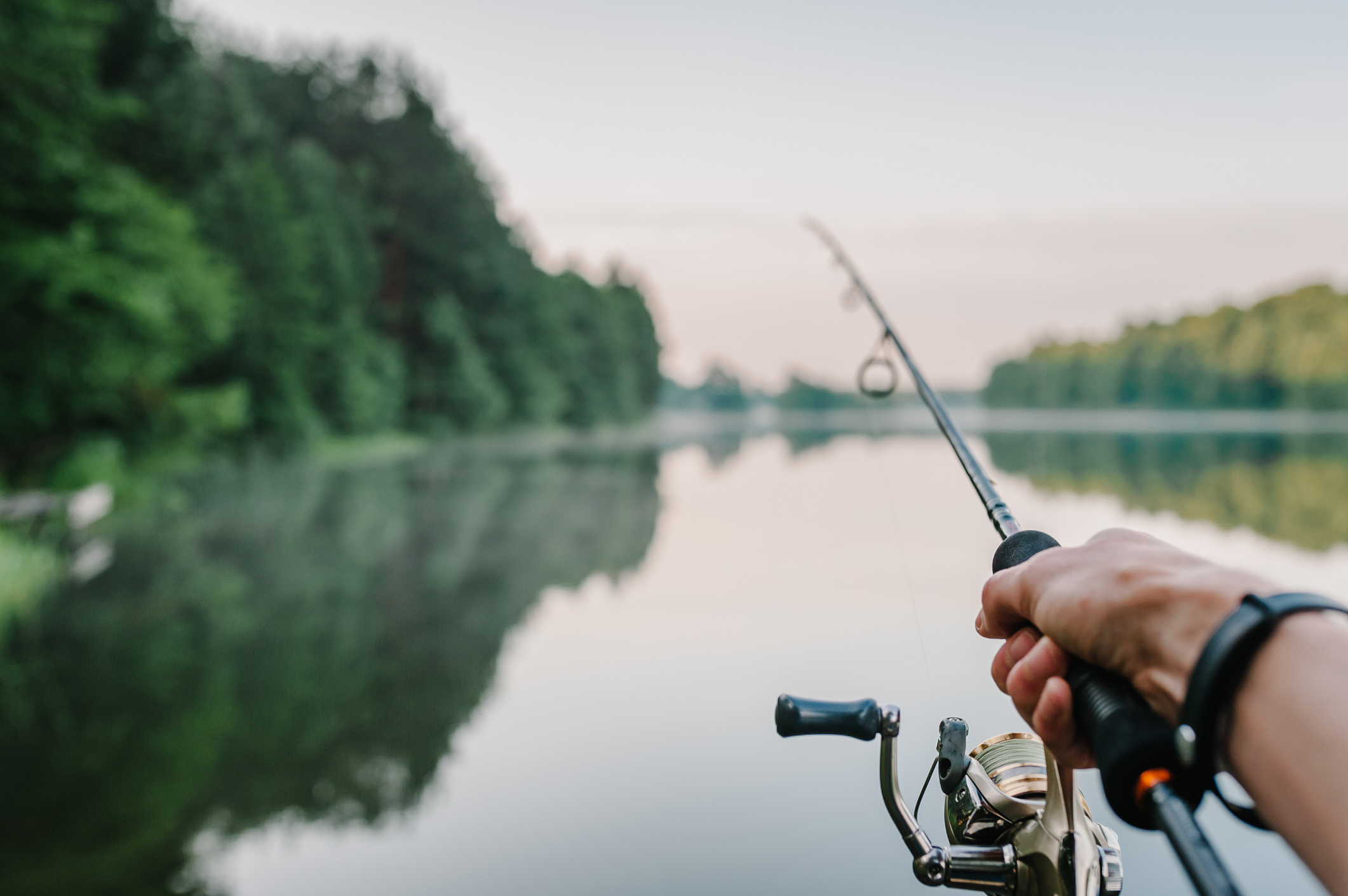 Fisherman with rod, spinning reel on the river bank. Sunrise. Fishing for pike, perch, carp. Fog against the backdrop of lake. background Misty morning. wild nature. The concept of a rural getaway.